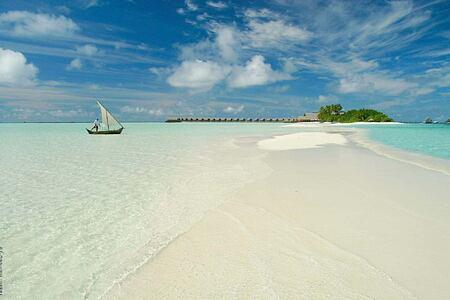 island with boat at Cocoa Island by COMO Resort Maldives