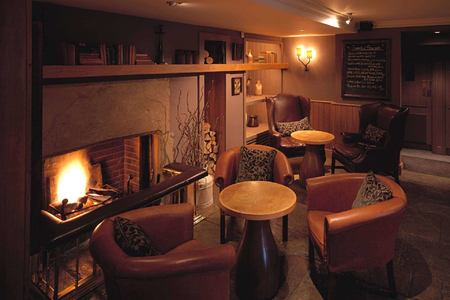 By the fire in the Gumstool Inn at calcot manor england uk