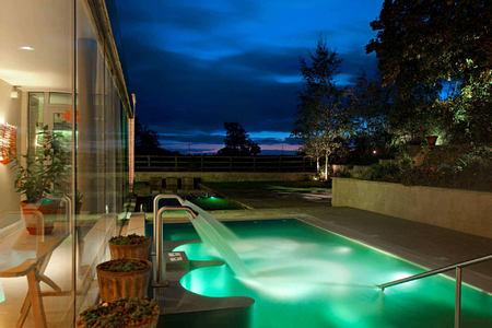 Side shot of hydrotherapy pool at night at barnsley house england uk