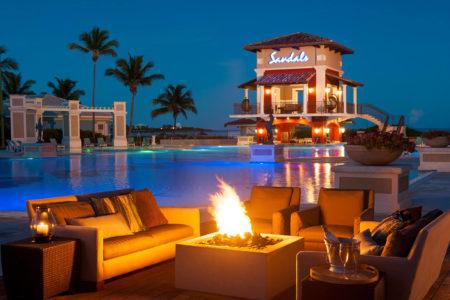 lit fire pits around the main pool at night at sandals emerald bay resort bahamas