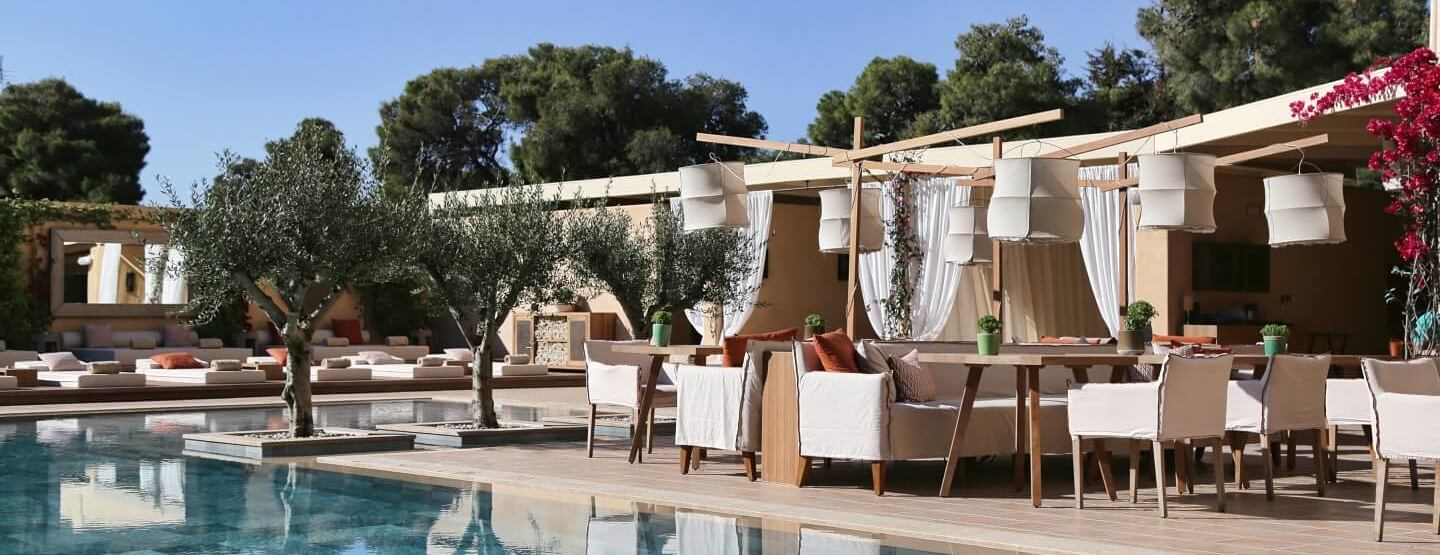 swiming pool and sun loungers and restaurant terrace at The Margi hotel