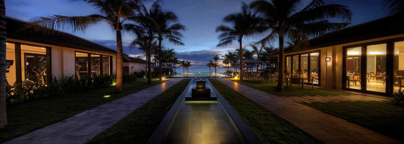 walkway to swimming pool and beach beyond at fusion maia resort vietnam