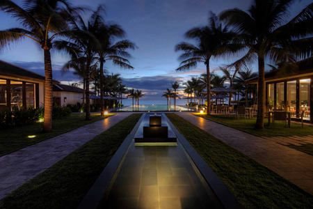 walkway to swimming pool and beach beyond at fusion maia resort vietnam