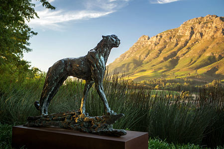Cheetah sculpture against a panoramic backdrop at Delaire Graff South Africa