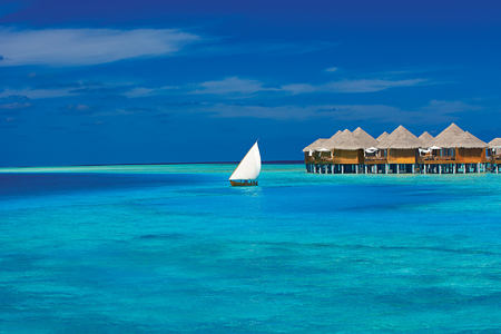 Exterior of huts and Dhoni at Baros Maldives