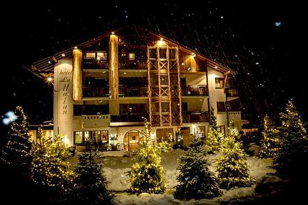 ront view during snowfall of Hotel La Majun Italy