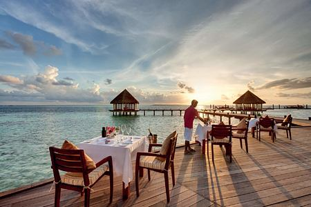 Dining tables in front of Matheefaru Sunset at Hideaway Beach Resort Maldives