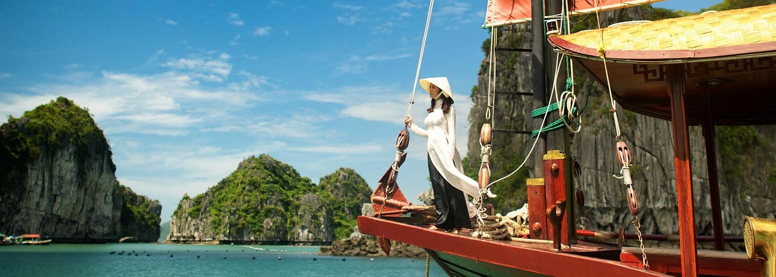 Girl in bow of boat with islands in the background in Vietnam