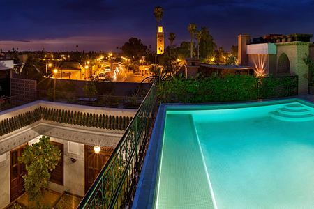 View of the Pool terrace and city at night at Villa des Oranges Morocco