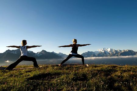 Two people enjoying Yoga with a backdrop of mountains at The Lodge Switzerland