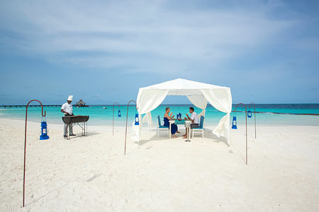 A couple dining on the beach at reethi beach resort maldives