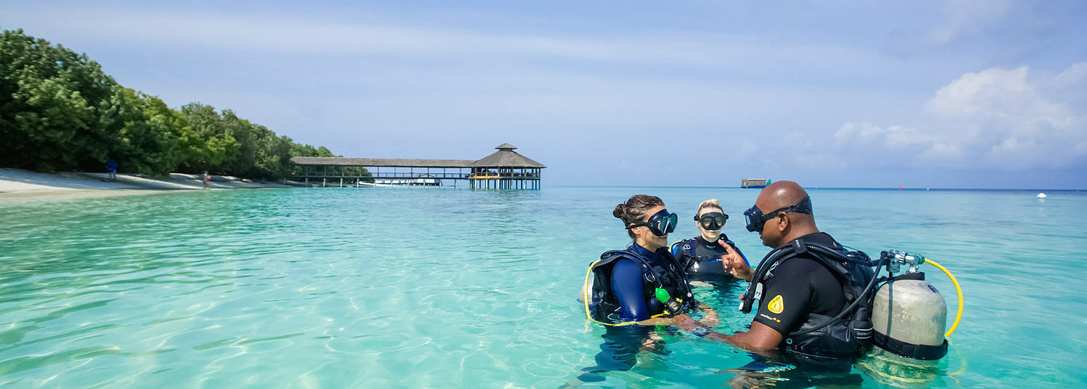 Two people being taught to scuba dive at reethi beach resort maldives