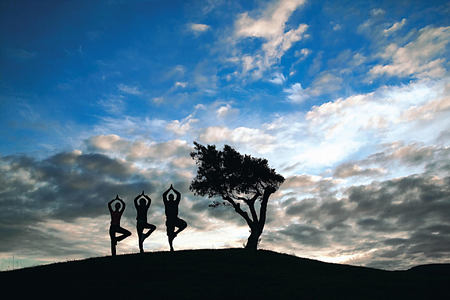 Three people practising yoga against the sky at Six Senses Douro Valley Portugal