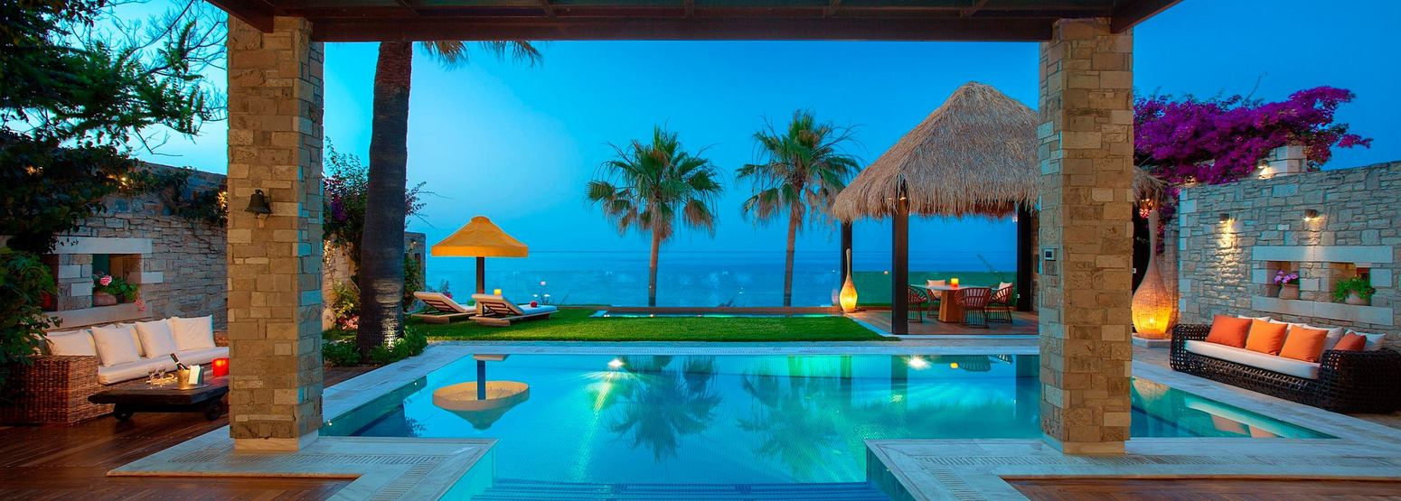Outdoor decking and pool area of a royal spa villa at dusk