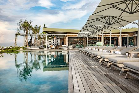Loungers facing the pool on the deck at the beach club COMO Canggu
