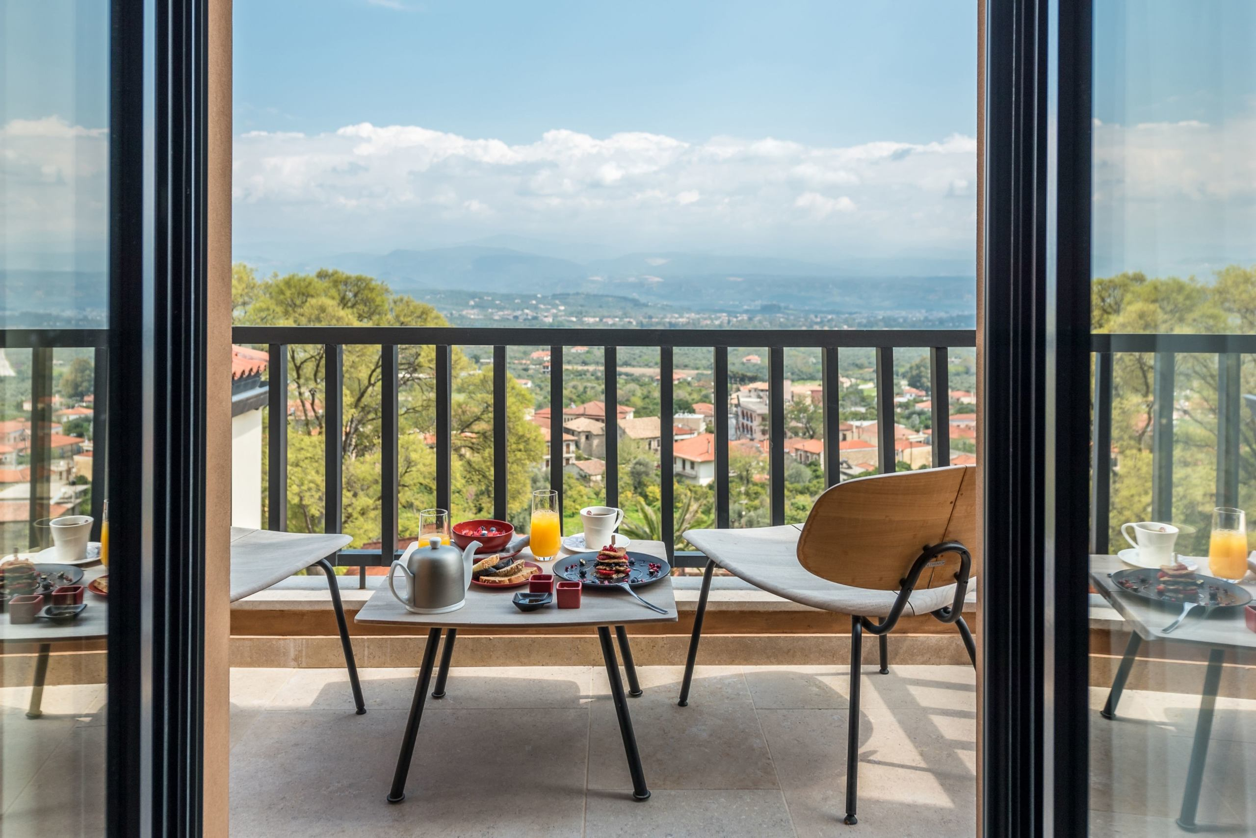 Breakfast being served on a balcony overlooking the Greek countryside