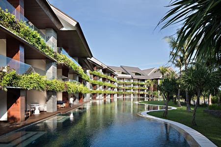 Exterior of COMO Canggu Bali featuring rooms, swimming pool and palm trees