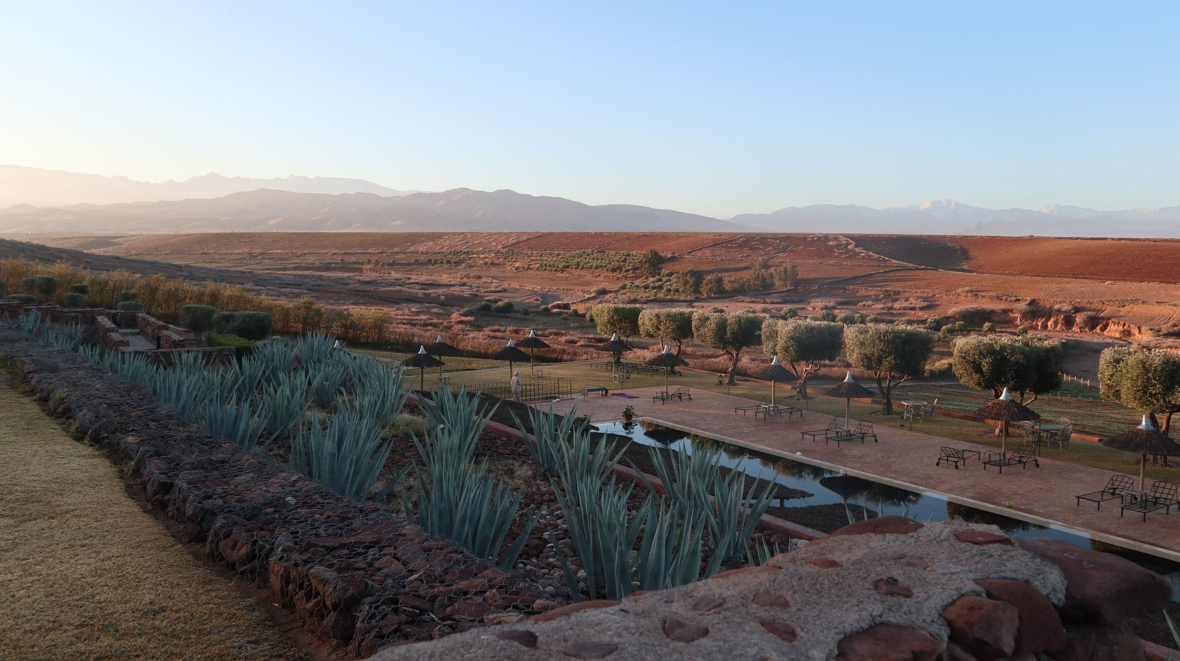 View across the pool at sunrise at Palais Paysan Marrakech