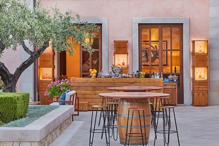 Bar terrace at dusk with barrell dining tables at Ses Oliveres restaurant